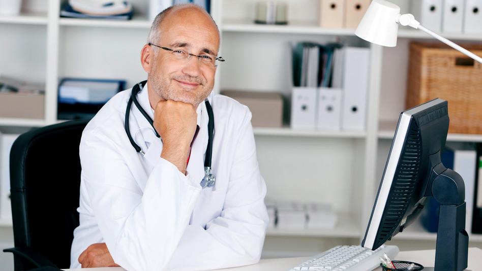 smiling-doctor-with-chin-on-hand-s-710400